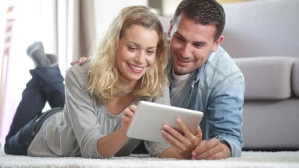 Boldog, fiatal pár szép a szőnyegen, a nappaliban, és használ egy tabletta