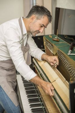 Technician tuning a upright piano using lever and tools