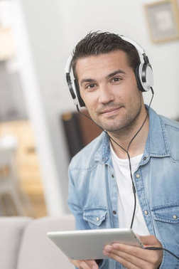 Portrait of handsome young man listenning music wwith a tablet a