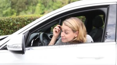 Young blond woman applying makeup while in the car