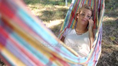 cheerful young woman using a phone in a hammock