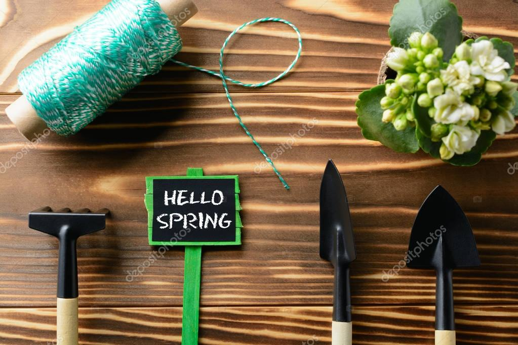 Hello Spring sign with tools on table