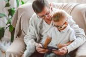 Fotografie Älterer Großvater und sein kleiner Enkel nutzen Tablet-Gerät
