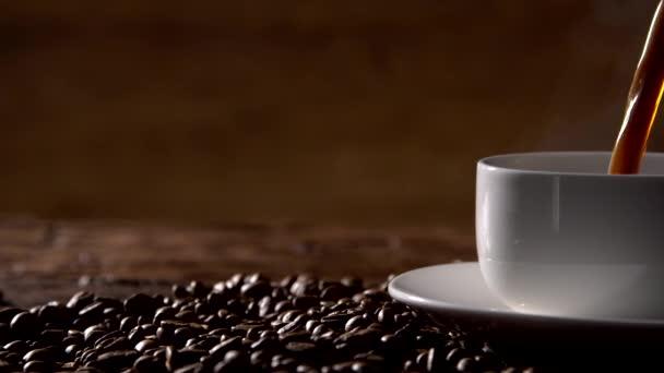 Nalil kávu z kávovaru bílých pohár obklopený kávová zrna.