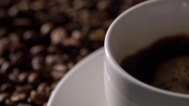 Kaffee aus Kaffeekanne in weiße Tasse gießen, umgeben von Kaffeebohnen.