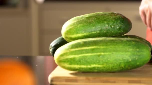 Nő szeletelés uborka. Női kezek vágott zöld uborka gyűrűk. Nagy késsel. A konyhában. Fa tábla. házias asszony. Friss uborka. Friss zöldségek