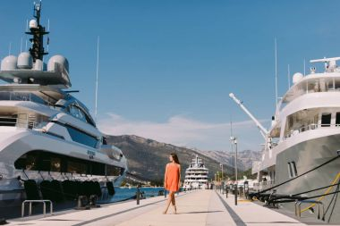 woman walking in sea port with yachts background. travelling on sea yacht