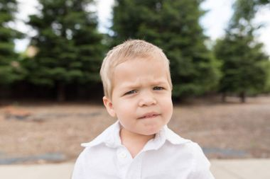 Young Toddler Portrait Outside Biting Lip