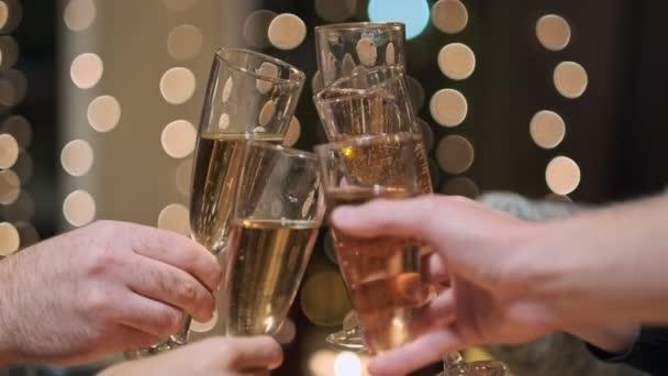 Koccintó pohár pezsgő. Toast ünnepli a karácsonyt. Sárga fények a háttérben. Sok a kéz. Egy baráti társaság..