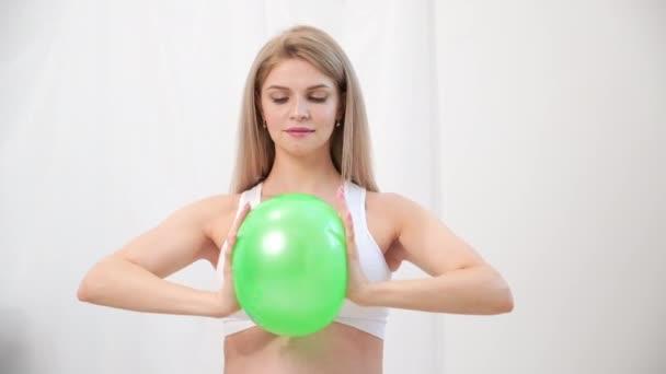 Eine junge schöne schwangere Kaukasierin sitzt auf dem weichen Teppich des Hauses. Er betreibt Fitness und macht Übungen. Sportbekleidung.