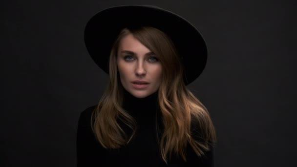 Portrét krásné mladé blondýny v černém klobouku s poli a svetrem. Smyslná emocionální žena..