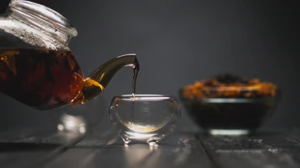 Teaszertartás. A nők kézzel öntik forró fekete tea virágokkal egy átlátszó teáskanna üveg piala csésze.