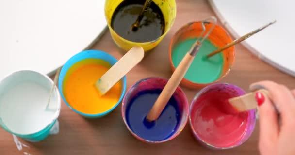 Umělkyně připravuje a hnětá barvy pro kreslení. Různé jasné barvy. Detailní záběr rukou.
