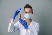 Vérvizsgálat. Egy női orvos tart egy kémcsövet paciets vérrel..