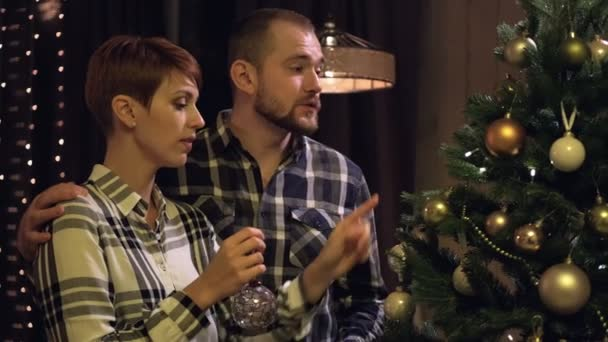 Young married couple at home in casual clothes, a man and a woman decorate the Christmas tree.