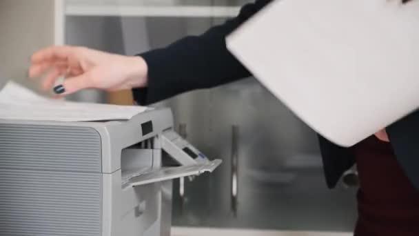 Eine junge Frau im Sakko, eine Büroangestellte druckt Dokumente auf einem Kopiergerät.