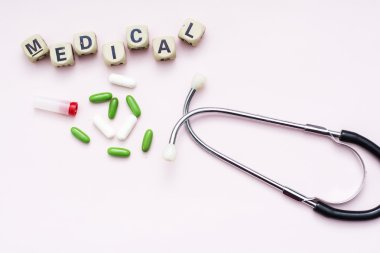 Pink background inscription medical, pills and stethoscope