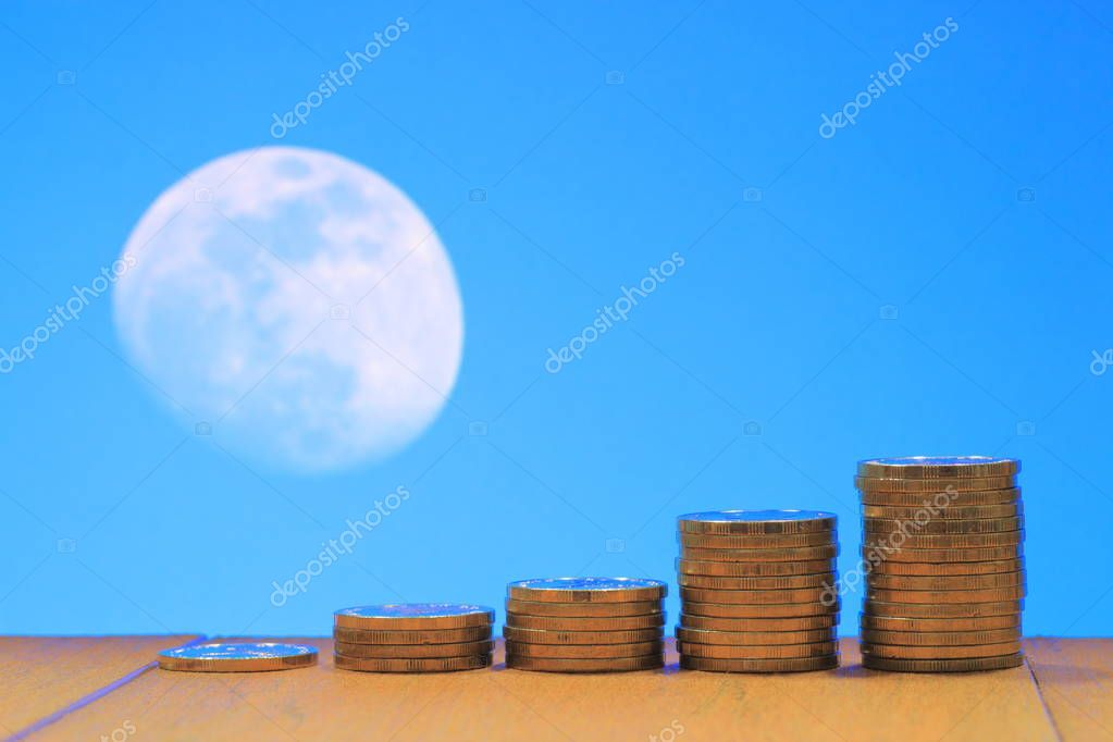 Dream cash Money fly to the moon travel concept. Coins pile stacked in increasing chart shape on wood board with Blue day sky and white moon background. For good business saving and money related concept