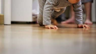toddler crawling on clean bedroom wooden floor while mother watching in the back. child development and baby growing up.