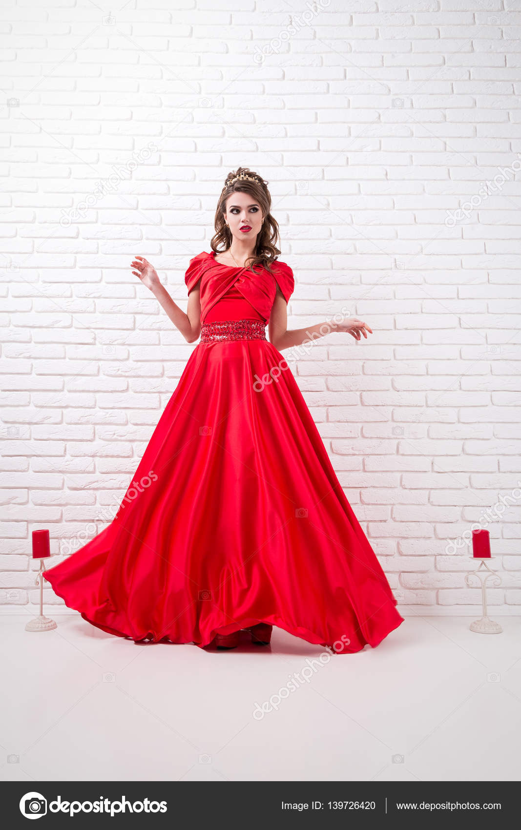 9fcfab4457f8 Donna elegante in un vestito rosso lungo sta levandosi in piedi in una  stanza bianca