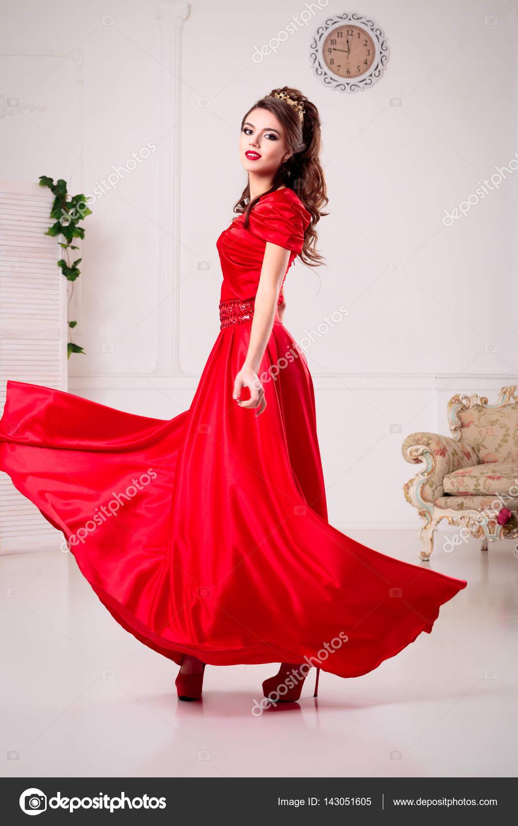 622b77107bf Une femme élégante dans une robe longue rouge est debout dans une salle  blanche chic