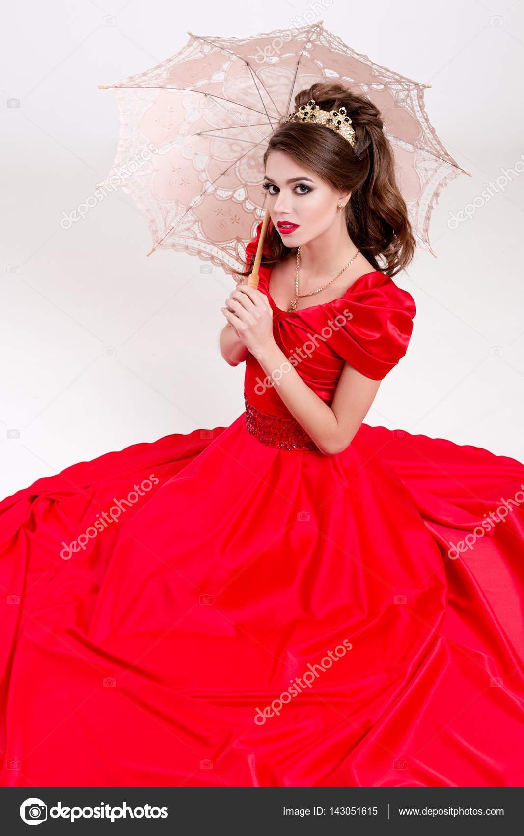 36ce5eb78191 Κομψή γυναίκα σε ένα μακρύ κόκκινο φόρεμα κάθεται στο πάτωμα και κρατώντας  μια ομπρέλα vintage– εικόνα αρχείου