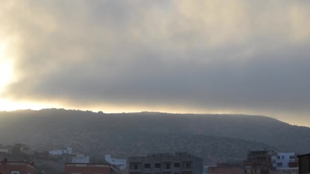 Timelapse Sunrise of bright yellow sun from behind mountains with fog in Morocco