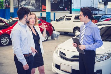 Successful business couple buying a new car at car dealership.