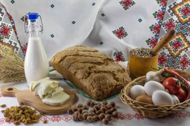 Bread, salted cheese, milk, raisins, sunflower seeds, garlic, tomatoes, hot pepper and hazelnuts on the background of Ukrainian towels