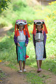 Photo Two beautiful asian young Lahu tribe girls in custom dress walk in village with smile and happy.