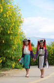 Photo Two young asian Lahu tribe girls in custom dress walk with smile and happy.
