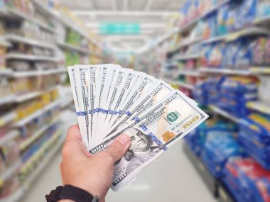 Hand hold American dollar USD banknote at shopping store blur background.Coronavirus covid-19 spread critical effect world economic people shock with stockpiling and hoarder goods run out of stock.