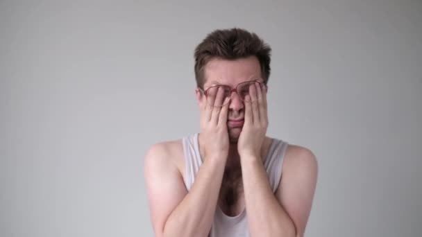 Caucasian funny young man in glasses with headache or hangover, rubbing his face