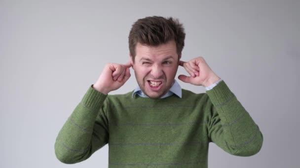Porträt eines ernsthaften jungen Mannes, der beide Ohren mit isolierten Händen auf dem grauen Hintergrund bedeckt