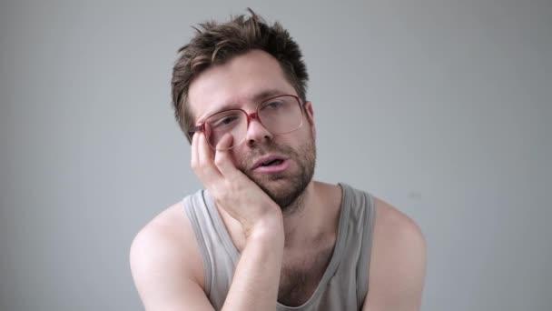 Unkempt férfi szemüvegben fejfájással buli után. Stresszes vagy beteg.