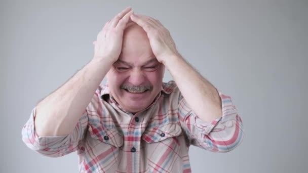 Rozrušený, vystresovaný starší nemocný, unavený muž po špatném dni v práci