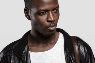Close up portrait of handsome African male model with healthy clean skin wearing leather jacket and shoulder bag, looking serious and thoughtful, posing agsaint white studio wall background