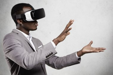 Close up of African employee wearing formal suit and goggles, experiencing virtual reality, stretching his arms as if holding something with his hands. Black man playing video games using oculus