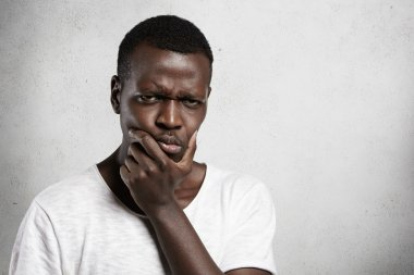 Portrait of skeptical African young man looking with suspicious or annoyed expression, holding hand on chin, doubting, thinking over something. Black male with disgust or disapproval on his face