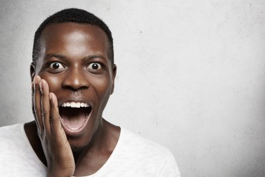 Human face expressions and emotions. African male screaming in surprise, mouth wide open, holding hand on his cheek, shocked with some unexpected news against copy space background for your content