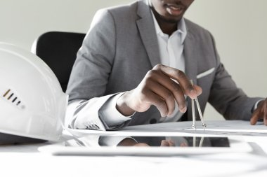 Construction concept. Engineering tools. Close-up of young African engineer or architect using compasses for drawing new housing blueprint project, sitting at desk with digital tablet and helmet