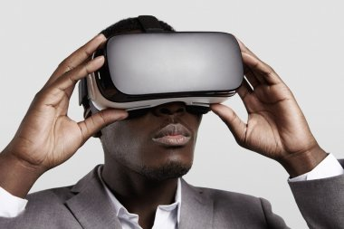 3d technology, virtual reality, entertainment, cyberspace concept. Young dark-skinned entrepreneur wearing formal suit using oculus rift headset with head-mounted display, playing video game in office
