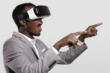Surprised African businessman using oculus rift headset, experiencing virtual reality while playing video game. Black man wearing 3d glasses, pointing his fingers as if interacting with something