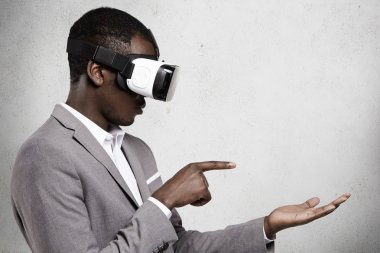 People, technology, entertainment and cyberspace concept. Young African businessman wearing suit and virtual reality headset, gestruring as if using some digital gadget while playing video game
