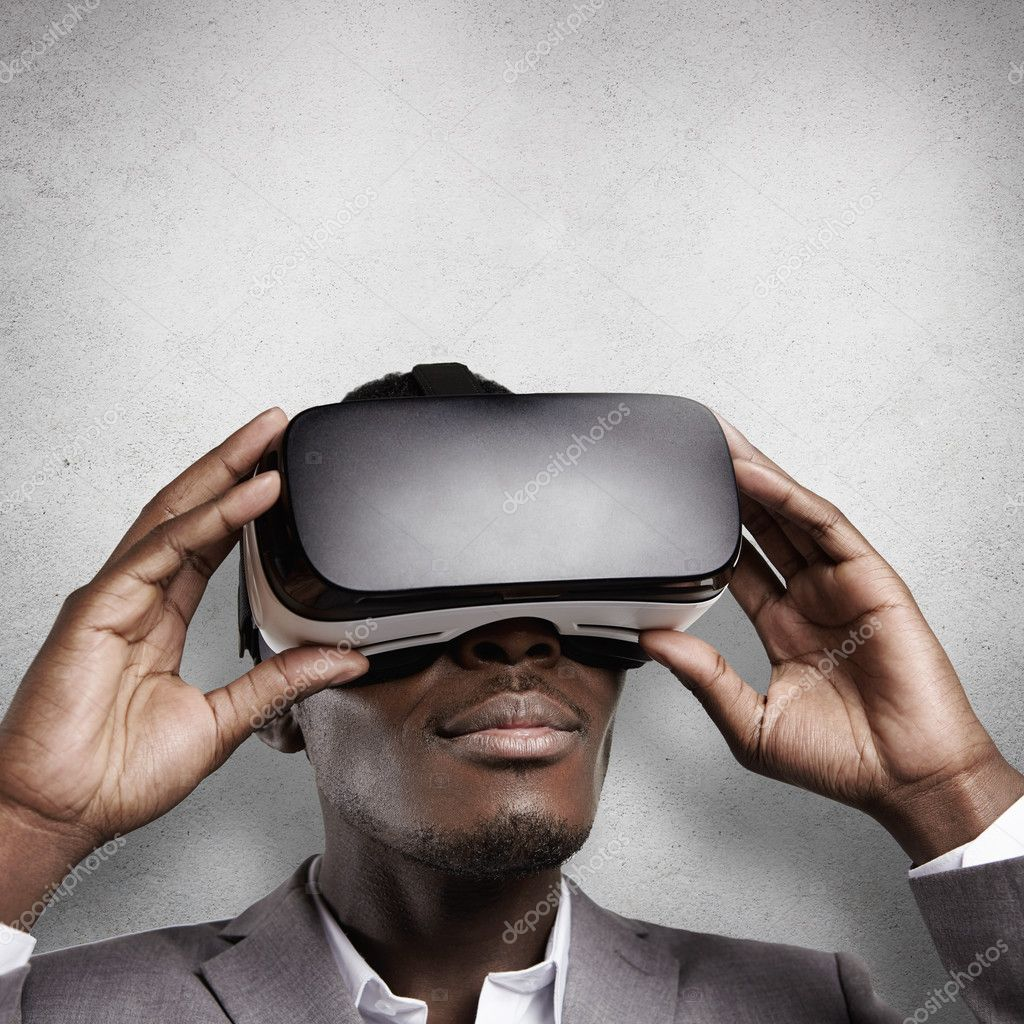 African office worker in formal wear, experiencing virtual reality, wearing  VR headset glasses. Black man using oculus, playing video games, looking  joyful ... 1a6590665249