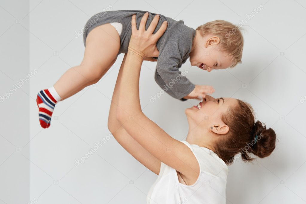 Nice shot of happy mother and child on the white background. Young attractive woman with bunch of brown hair rising blond son, sincerely smiling. Pleased baby touching her face in endless joy.