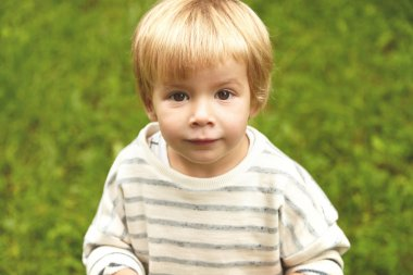 Charming close-up innocent portrait of little innocent kid. Calm Caucasian boy with blond hair, round brown eyes looking at camera. Five-years old infant standing still on fresh green grass background