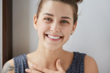 Portrait of happy Caucasian girl with bun of brunette hair, tattoo on her shoulder and stripped top. Attractive female smiling with all her white teeth, putting her hand on chest in endless joy.