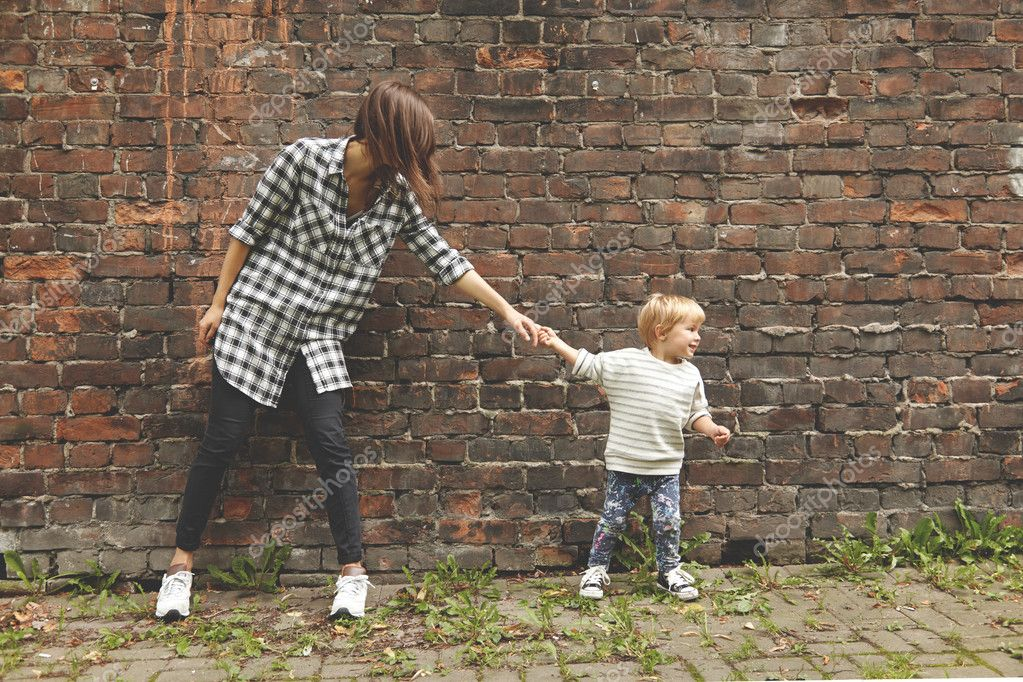 Little nephew pulling her elder aunt to go further. Young girl in checked shirt, black trousers standing at place near brick wall. Tiny kid in jeans and stripped sweater wants her aunt to follow him.