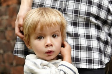Nice shot of blond innocent boy with brown eyes. Lovely childish facial expression with slightly open mouth. Baby standing near young mother in checked shirt. Mom stroking kid's head near brick wall.